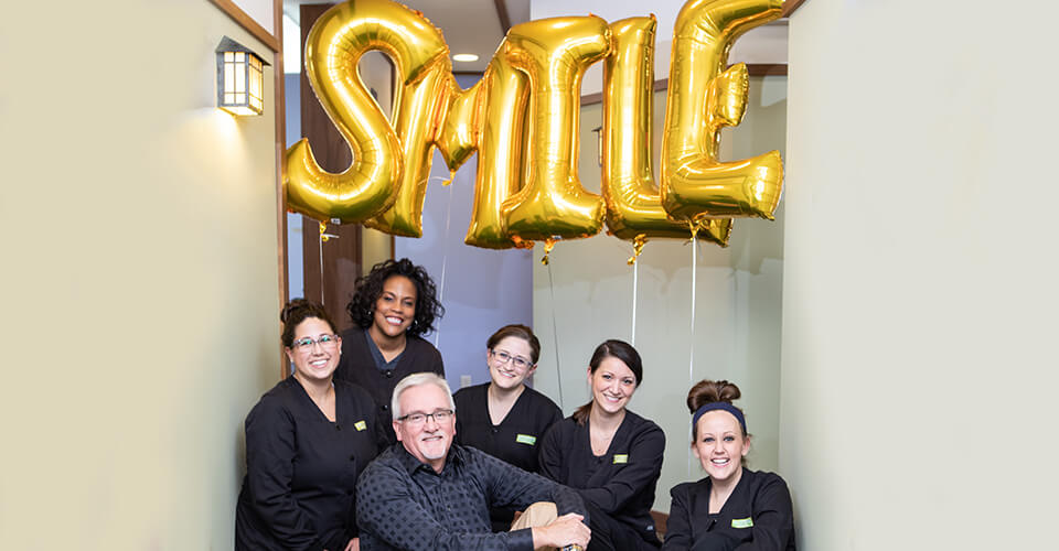 The Keystone Dentistry team posing with balloons that say smile