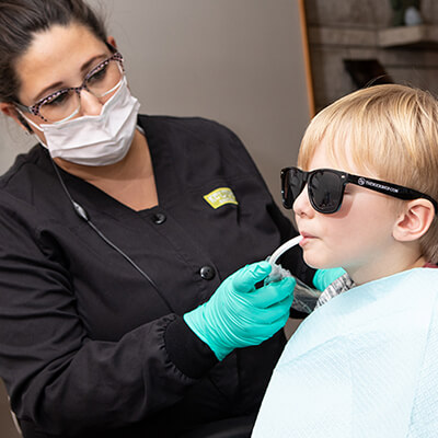 Our dental hygienist performing a pediatric dentistry exam on a little kid wearing sunglasses