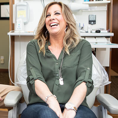 A female patient laughing in the dentist chair