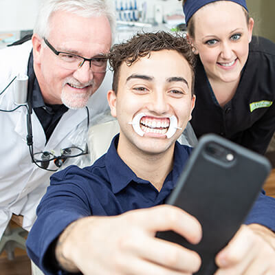 Dr. Kinney, a patient, and team member taking a selfie after a successful cosmetic dentistry visit