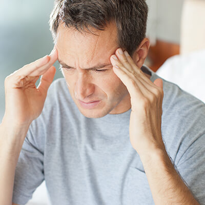 Man wearing grey shirt and holding his head with both hands because he needs restorative dentistry