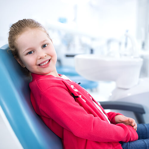 A little girl sitting in the dentist chair and smiling while experiencing children's dentistry