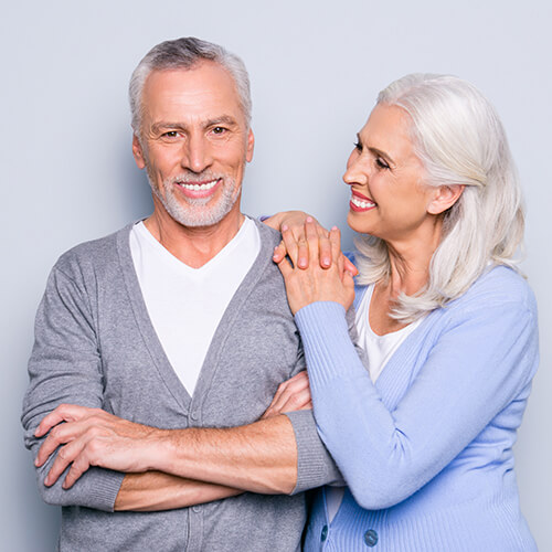 An elderly couple smiling with beautiful teeth