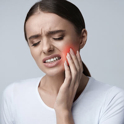 Woman holding the side of her face in pain because she needs family dentistry