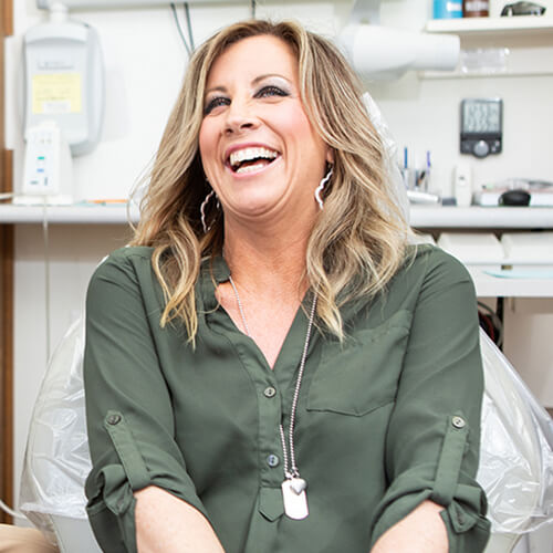A female patient laughing while waiting to receive restorative dentistry and sitting in the dentist chair