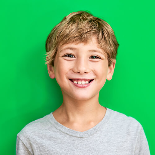 Little boy with fair hair smiling in front of a green background