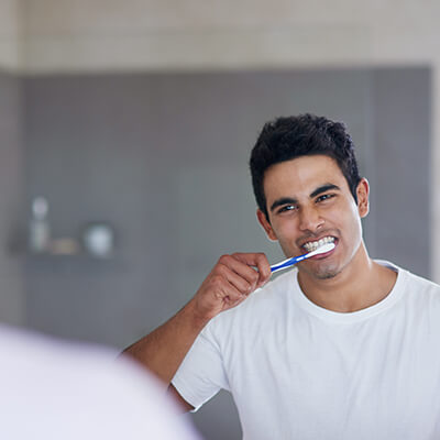 A middle-aged man wearing a grey shirt and brushing his teeth