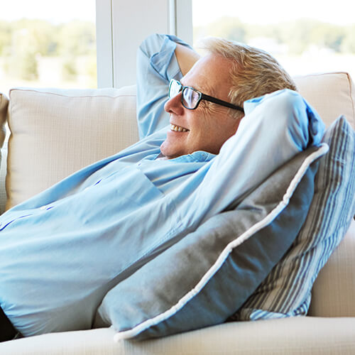 A mature man relaxing on the couch because his Indianapolis dentist makes dentistry a breeze with sedation dentistry option.
